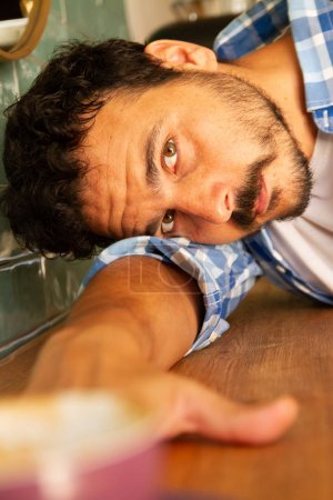 Photo pour Jeune homme se penchant sur une table de cafétéria semblant sérieuse - image libre de droit