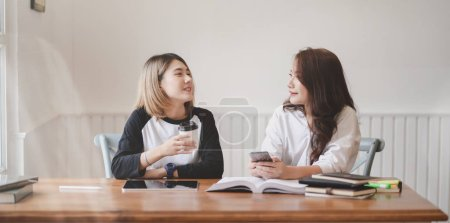 Two adorable young female freelancers chatting tog...