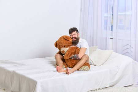 Photo pour Ne jamais grandir concept. Le mec au visage heureux étreint un ours en peluche géant. Macho avec barbe et moustache câlins avec peluche jouet. Homme assis sur le lit et câlins gros jouet, rideaux blancs sur le fond . - image libre de droit