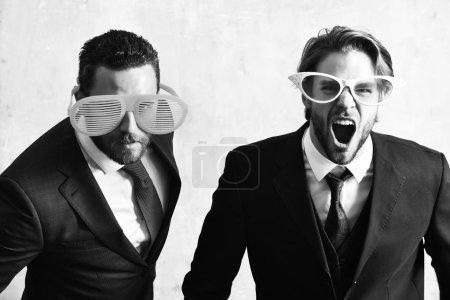 Photo pour Concept de relation de bureau. beaux hommes d'affaires barbus avec des lunettes drôles et costume d'affaires élégant ayant fête - image libre de droit