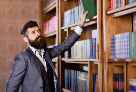 Photo for Vintage style and fashion. Bearded man in expensive suit in his cabinet. Professor stands in big library and holds book. Mature man with serious face. Study, teach, history, literature concept. - Royalty Free Image