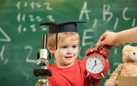 Photo for Kid boy in academic cap near clock in male hand, classroom, chalkboard on background. School break concept. Child on smiling face looks at alarm clock. Pupil waiting for school break. - Royalty Free Image