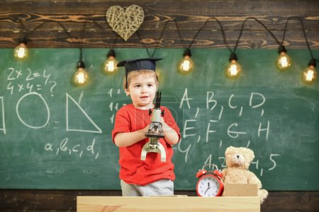 Photo for Smart kid concept. First former interested in studying, learning, education. Child on happy face holds microscope. Kid boy in academic cap work with microscope in classroom, chalkboard on background. - Royalty Free Image
