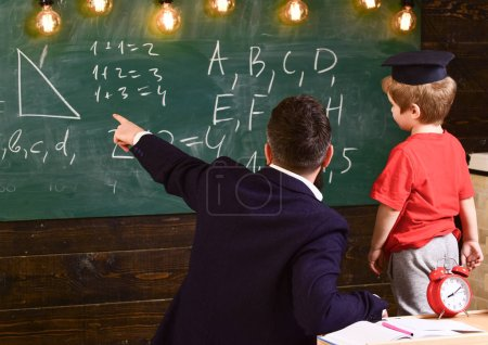 Young male teacher guides his child student to learning while pointing and looking at chalkboard with scribbles on, sitting in classroom, rear view