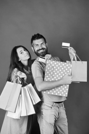 Guy with beard and girl with happy faces do shopping.