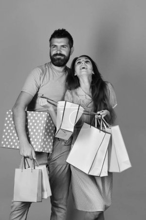 family shopping. Couple in love holds shopping bags on yellow background