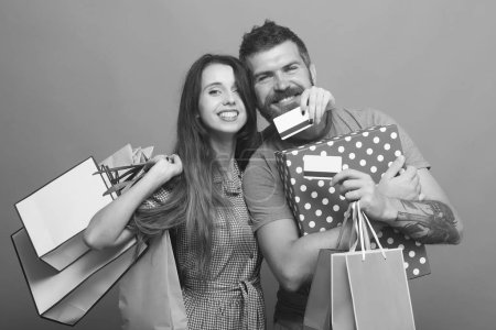 Couple in love hugs holding shopping bags and credit cards on blue background. Guy with beard and lady do shopping. Bearded man with smiling face holds pink packets. Shopping and fashion concept.