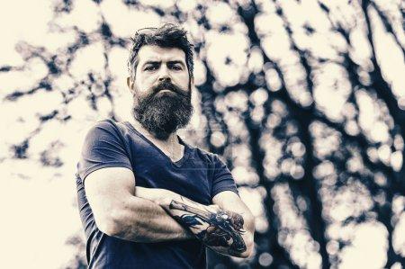 Photo pour Salon de coiffure et concept de style. Homme barbu en tenue décontractée posant en plein air. Homme à longue barbe semble élégant et confiant. Homme avec barbe et moustache sur le visage strict, arbres sur le fond, déconcentré . - image libre de droit