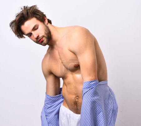 Photo for Macho with sexy body takes off home or bath clothes. Morning and masculinity concept. Man with beard in blue dressing gown on white background. Guy in blue bathrobe with sexy torso and six packs. - Royalty Free Image