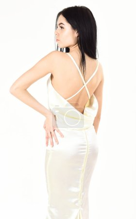 Photo for Fashion wedding concept. Woman in elegant white dress with nude back, white background. Fashion model demonstrate expensive fashionable evening dress or wedding dress. Bride, graceful girl in dress. - Royalty Free Image