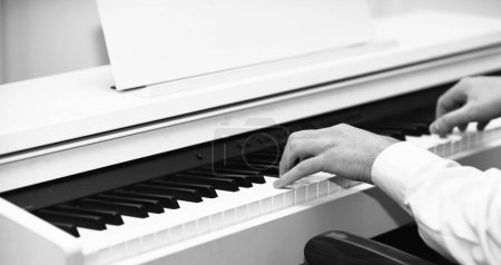 Photo for Live music concept. Music performers hands with white cuffs playing piano. White piano with black keyboard and musicians hands. Male hands creating music on white piano background. - Royalty Free Image