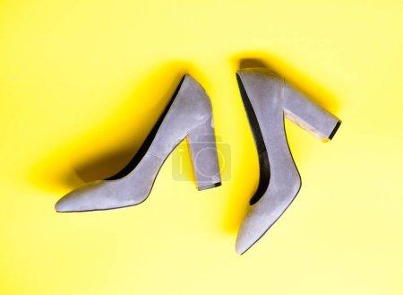 Photo pour Concept de chaussures en daim. Paire de chaussures à talons hauts tendance. Chaussures en daim gris sur fond jaune. Chaussures pour femmes avec talons hauts épais, vue de dessus . - image libre de droit