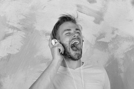 Foto de Estilo de vida musical. El hombre europeo se divierte. Americano guapo barbudo con auriculares. Hipster de ojos azules con estilo y smartphone. Alegre adolescente dj escuchar canciones a través de auriculares . - Imagen libre de derechos