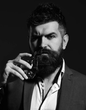 Photo for Drinking and alcohol concept. Man with serious face toasting with glass of alcohol. Businessman ready to drink cognac or brandy. Connoisseur with beard and bourbon or whiskey on black background. - Royalty Free Image