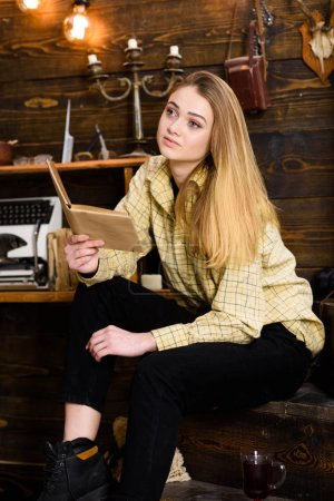 Photo for Girl student study with book in house of gamekeeper. Study concept. Lady on calm face in plaid clothes looks cute and casual. Girl in casual outfit sits with book in wooden vintage interior. - Royalty Free Image