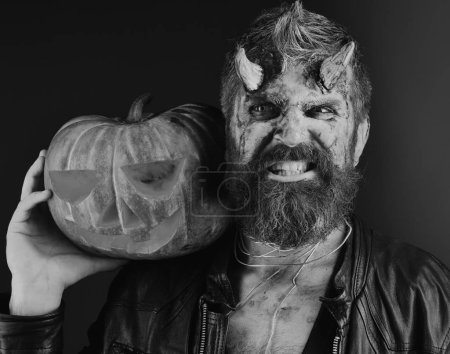 Photo for Devil or monster with October decorations. Demon with horns and evil face holds carved jack o lantern. Halloween party concept. Man wearing scary makeup holds pumpkin on bloody red background. - Royalty Free Image