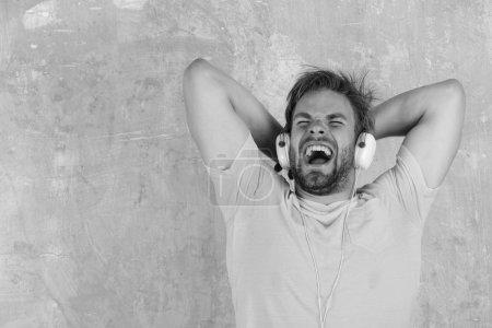Photo pour Mode de vie musicale. L'homme européen s'amuser temps. Dj gai écoute chansons via écouteurs. Américain beau barbu mec avec un casque. Les bleus de hipster élégant Smartphone. - image libre de droit