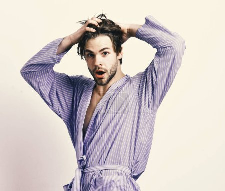 Photo for Morning and showering concept. Man with beard in blue dressing gown on grey background. Bearded macho in blue bathrobe or leisure wear. Guy touches hair in home or bath clothes. - Royalty Free Image
