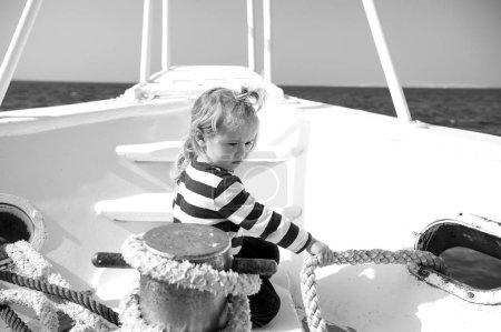 Photo pour L'enfant tire la corde sur le yacht par une journée ensoleillée. Garçon en chemise de marin naviguer en mer bleue. Aventure, découverte, errance. Destination de voyage, croisière, voyage. Concept vacances d'été . - image libre de droit