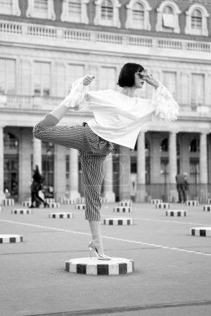 Photo pour Yoga, pilates fitness sport à Paris, France. Fille en chaussures à talons hauts, vêtements à la mode. Mode style beauté, style de vie. Vacances, concept de voyage. Femme étirer jambe sur carré - image libre de droit