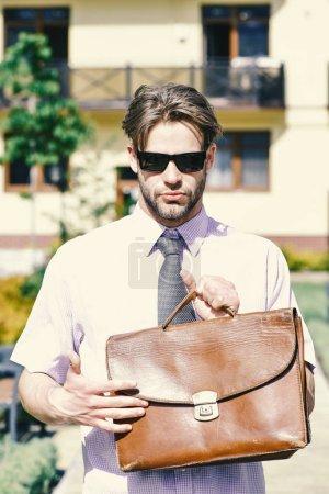 Photo pour Agent immobilier détient porte-documents. Jeune homme d'yard de la maison d'habitation sur une journée ensoleillée. Homme chemise avec une cravate ou homme d'affaires avec un visage calm avec s'appuyant sur le fond. Concept et immobilier. - image libre de droit