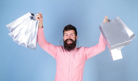 Photo for Man with stylish beard and mustache carrying shopping bags. Winner of luxury boutique gift certificate isolated on blue background. Bearded man in pink shirt with cheerful face, happiness concept. - Royalty Free Image