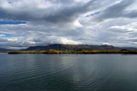 Photo pour Eau de mer sur la côte montagneuse sous un ciel nuageux à Rejkjavik, Islande. Mer sur paysage montagneux. Beauté de la nature sauvage. Météo et écologie. Wanderlust et vacances . - image libre de droit