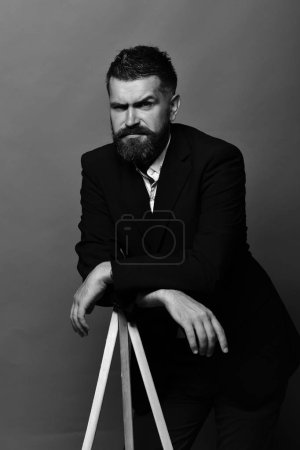 Photo for Art and style concept. Macho man leans on tripod on red background. Artist with stylish hairdo and doubtful face. Man with beard and stylish moustache wearing classic suit. - Royalty Free Image