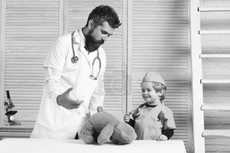 Photo pour Homme et garçon avec seringue sur fond en bois. Père et enfant avec des visages heureux jouant au docteur. Santé et concept d'enfance. Vet et petit assistant font l'injection à l'ours en peluche . - image libre de droit