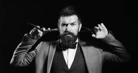 Photo for Businessman with serious face isolated on black background. Macho in formal suit cuts and shaves beard. Man with long beard holds shaving razor and scissors. Business and barbershop service concept. - Royalty Free Image