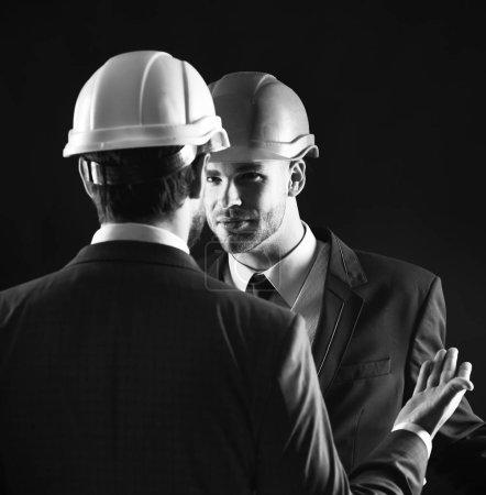 Photo pour Collaborateurs en costume formel et casques de construction. Concept d'entreprise de construction. Architecte technique s'entretient avec le chef de projet avec le visage grave. Ingénieurs avec des visages calmes isolées sur fond noir. - image libre de droit