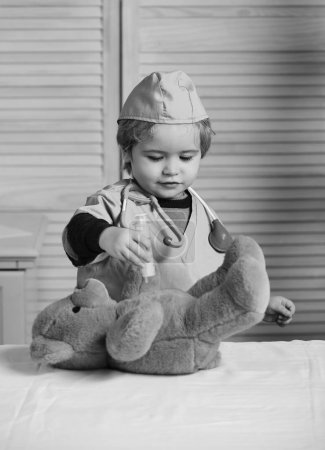 Photo for Kid in doctor coat makes injection to teddy bear. Boy in surgical uniform holds syringe on wooden background, defocused. Medical education and childhood concept. Child with serious face playing doctor - Royalty Free Image