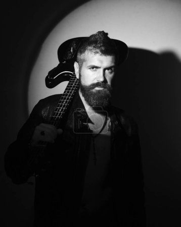 Photo for Musician and musical instrument in light directed on him. Guitar player with confident face on black background. Electric guitar on bearded mans shoulder. Music and hard rock style concept - Royalty Free Image