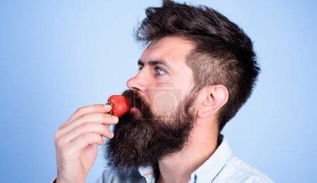 So schmeckt Sommer. Erdbeere gesunder Snack. Mann gut aussehender Hipster mit langem Bart, der Erdbeere isst. Beeren Saison Konzept. Hipster genießen saftige reife rote Erdbeeren. Mann genießt Beerenaroma
