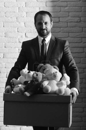 Photo pour Concept d'entreprise et de volontariat. L'homme à la barbe et au visage gentil fait un don. L'homme d'affaires porte un costume et une cravate intelligents. Leader tient boîte pleine de jouets sur fond blanc mur . - image libre de droit