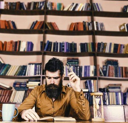 Photo pour Enseignant ou étudiant barbu étudiant à la bibliothèque. Homme au visage occupé à lire le livre, étagères sur fond. Éducation et science concept. Lecture scientifique, assis à table avec tasse et sablier . - image libre de droit