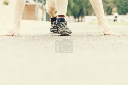 Photo for Trainers of runner starting his marathon on flat treadmill on outdoor stadium background, selective focus. Idea of sportive lifestyle and running - Royalty Free Image