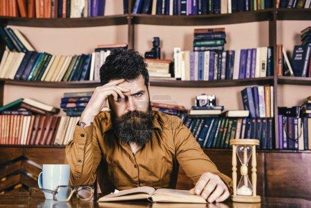 Photo pour Enseignant ou étudiant barbu étudiant à la bibliothèque. Homme sur le visage concentré livre de lecture, étude, étagères de bibliothèque sur fond. Concept d'auto-éducation. Homme assis à table avec tasse et sablier . - image libre de droit