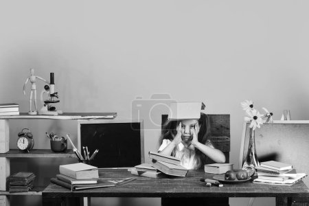 Photo for Kid and school supplies on yellow wall background. Homework and study time concept. Girl sits at desk with books, flowers, fruit and colorful stationery. Schoolgirl with bored face holds book on head. - Royalty Free Image