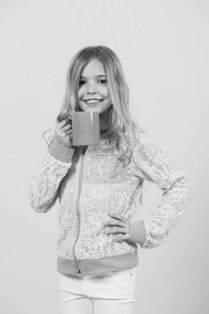 Photo pour Joyeux enfant souriant avec une tasse à la main. Fille sourire avec tasse bleue sur fond orange. Nourriture et boisson. Bonjour, concept petit déjeuner. Humeur thé ou café, pastel punchy. rhume, grippe. - image libre de droit