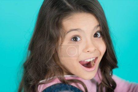 Photo pour Enfants surpris à pleine bouche sur fond bleu. Fille heureuse avec des cheveux brunette longtemps en bonne santé. Exceptionnelle beauté pour le visage exceptionnel. Soins dentaires. Salon de beauté. - image libre de droit