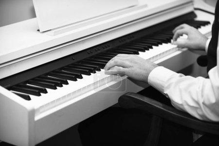 Photo pour Concept de pianiste. Mains masculines créant de la musique sur fond de piano blanc. Des interprètes de musique avec des poignets blancs jouant du piano. Piano blanc avec clavier noir et mains de musiciens . - image libre de droit