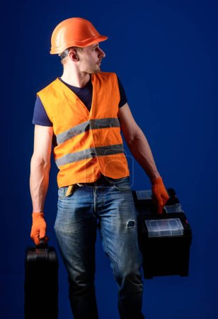 Photo for Worker, handyman, repairman, builder on calm face carries bags with professional tools. Equipped repairman concept. Man in helmet, hard hat holds toolbox and suitcase with tools, blue background. - Royalty Free Image