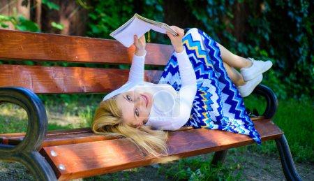 Photo pour Un livre intéressant. Intelligente et jolie. Belle dame relaxante. Fille reposer banc parc détente avec livre, fond vert de la nature. Femme passer du temps libre avec le livre. Fille lecture en plein air tout en se relaxant sur le banc . - image libre de droit