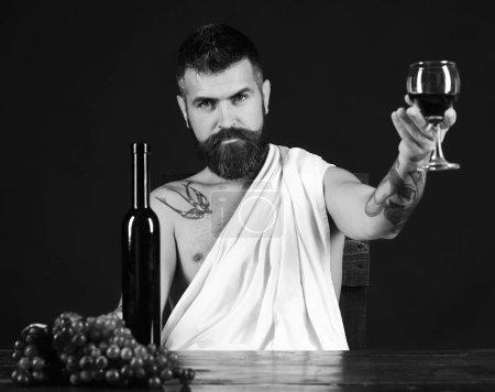 Sommelier schmeckt Getränk. Mann mit Bart hält Glas Wein auf braunem Hintergrund.