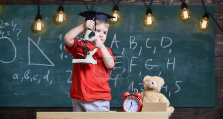 Photo for Smart kid concept. First former interested in studying, learning, education. Kid boy in academic cap work with microscope in classroom, chalkboard on background. Child on busy face near microscope. - Royalty Free Image