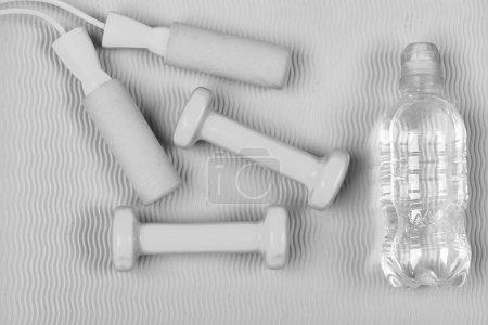 Photo pour Cloches et corde à sauter à côté de la bouteille d'eau. Sport et mode de vie sain concept. Haltères et corde à sauter de couleur bleu cyan sur fond de texture ondulée verte. Appareils de façonnage et de conditionnement physique - image libre de droit