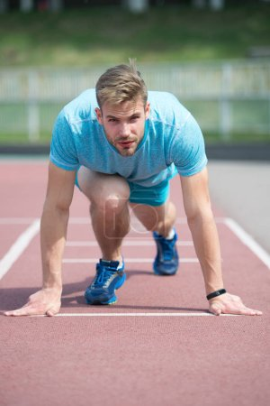 Photo for Start of sport career. Man runner on start position stadium background. Sportsman run outdoor at running track. Runner start position running surface. Sportsman on concentrated face ready to go. - Royalty Free Image