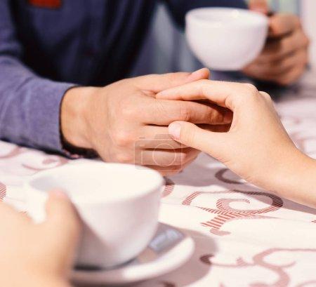 Photo pour Femme et homme ont rendez-vous. Mains sur la table, hommes et femmes, déconcentrés. Rendez-vous et concept de pause café. Couple amoureux tient des tasses de café à table . - image libre de droit