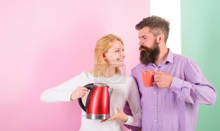 Photo for Spending good morning together. Couple prepare morning drink electric kettle device. Electric kettle boils water very quickly. Prepare favourite drink in minutes. Modern devices make our life easier. - Royalty Free Image